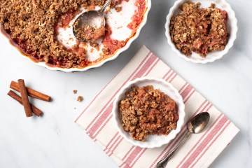 Landscape orientation of a scene of Rhubarb Crisp (Paleo/AIP) with a messed up serving dish and two small dishes with servings in them. There are cinnamon sticks and crumbs on the surface nearby.