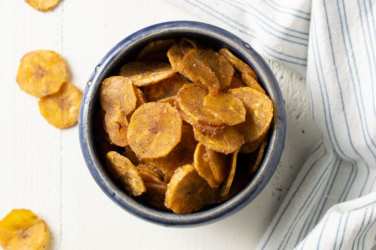 Flatlay of Sweet & Salty Plantain Chips in a blue bowl, with a white and blue striped cloth nearby.  Some chips have fallen out of the bowl.
