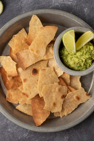 Landscape Flatlay of Corn-free Tortilla Chips in a tin pan, with a dish of guacamole and limes nearby. The scene is on gray concrete with lime wedges and an avocado.