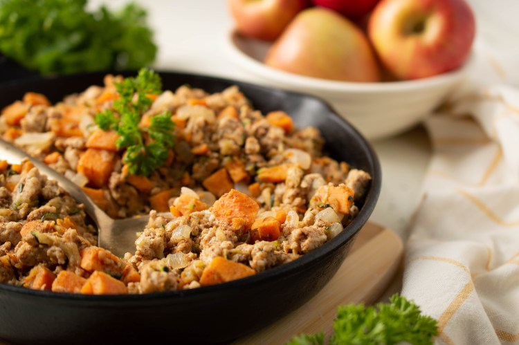 Turkey Breakfast Hash in an iron skillet on a cutting board with a bowl of apples nearby