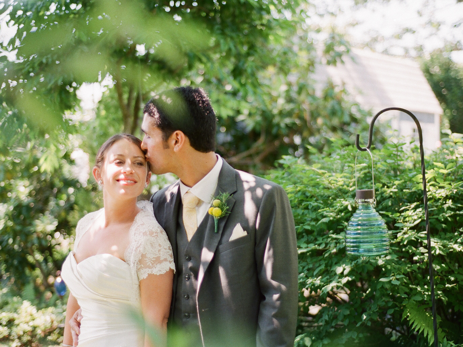 groom kissing bride on forehead with many green leaves in fore and background