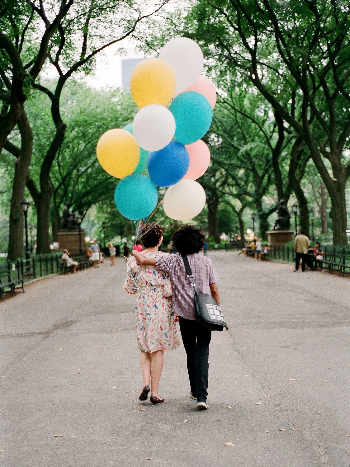 couple walking away with bouquet of large balloons