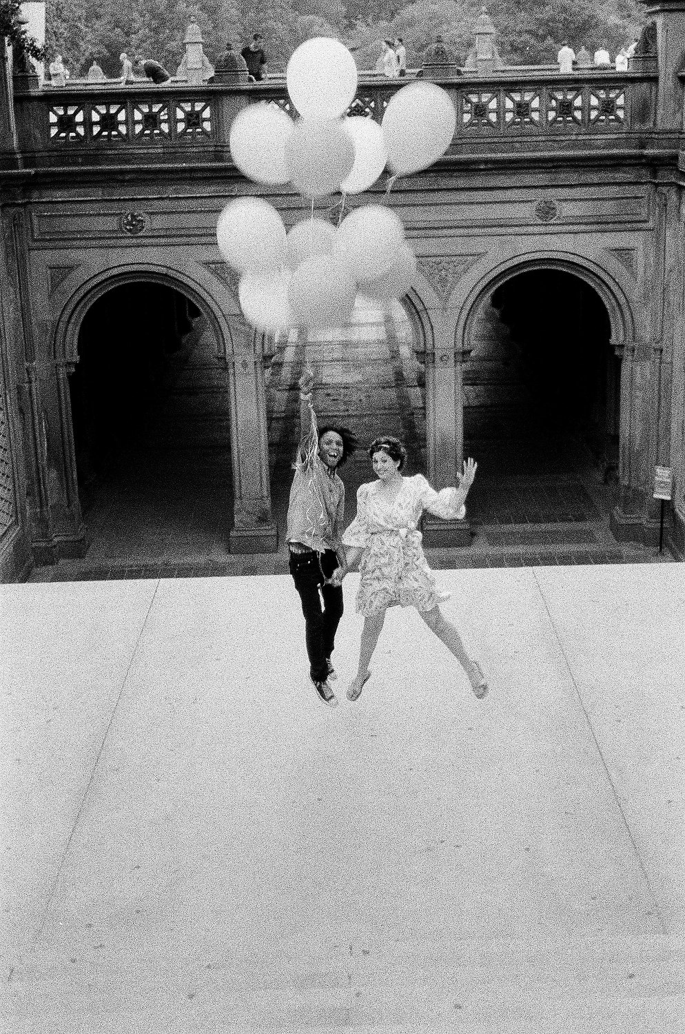 black and white photo of couple being carried away by balloons