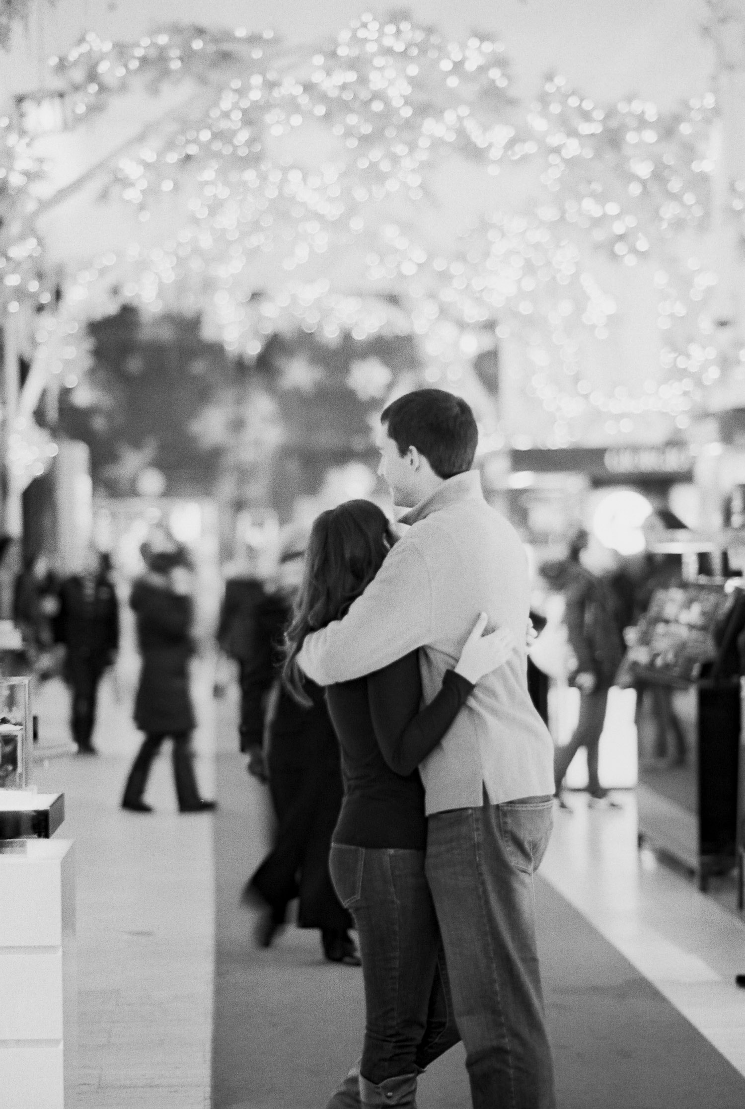 engaged couple hugging at saks in new york
