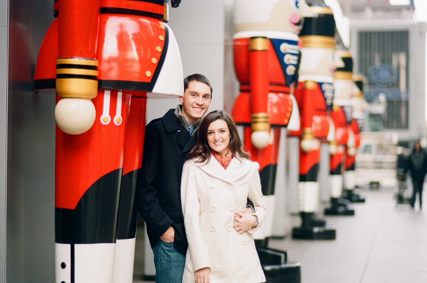 engaged couple smiling with toy soldiers in nyc