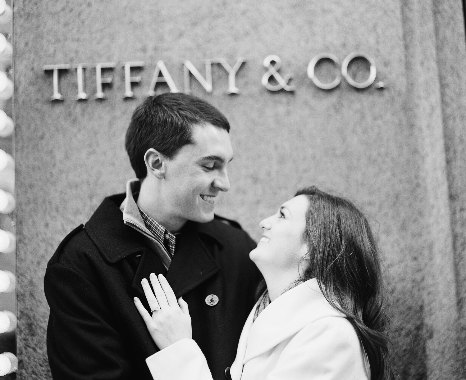 black and white photo of couple laughing in front of tiffany's