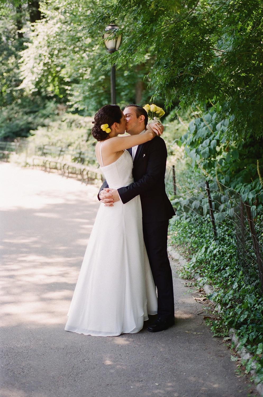 film photo of bride and groom embracing on walkway in park