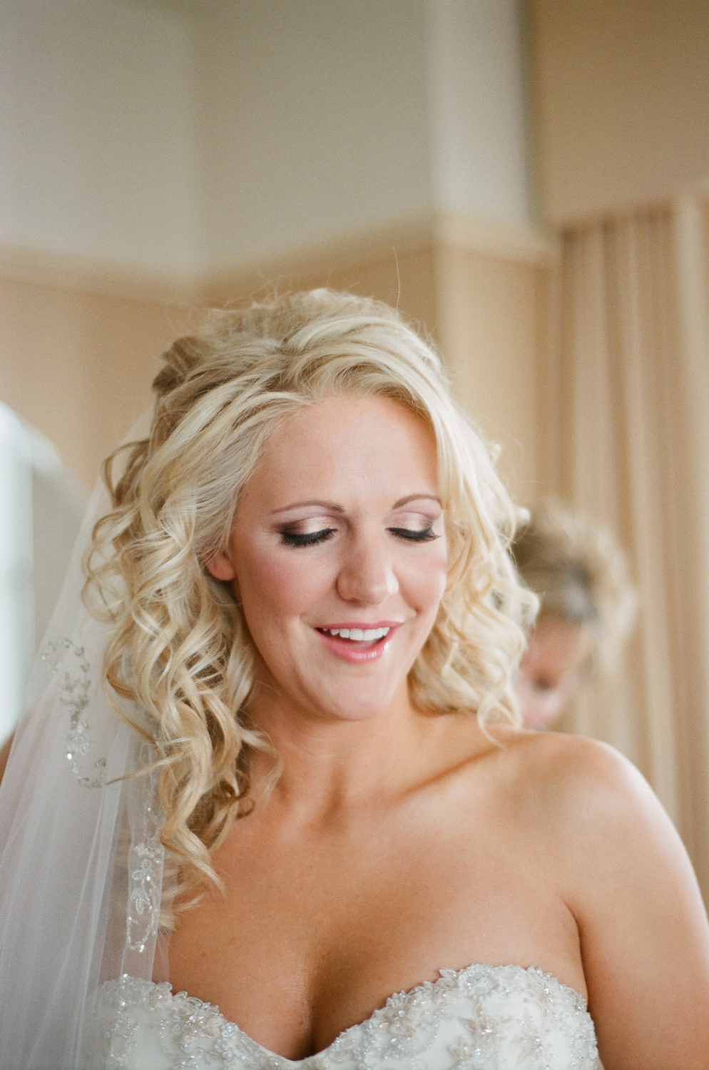 bride smiling while getting dressed