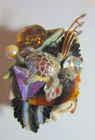 The main character in this Rose Quartz Cockatoo in Jeweled Jungle Wristy is rose quartz and a transparent blue mineral.