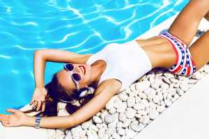 woman laying by the pool listening to music