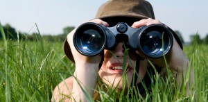 woman with binoculars in grass