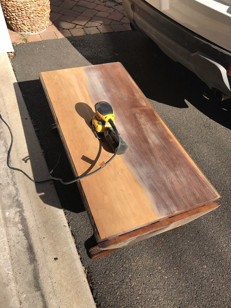 Sanding the top of vintage table