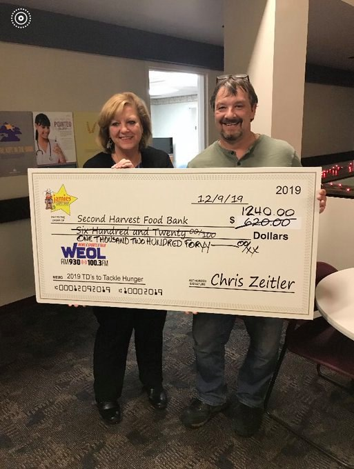 Chris Zeitler with Jamie's Carpet Shop and Susan Bartosch with Second Harvest Food Bank pose for the Touchdowns to Tackle Hunger check presentation! Chris decided to double the donation!! A $1,240 donation to Second Harvest Food Bank!