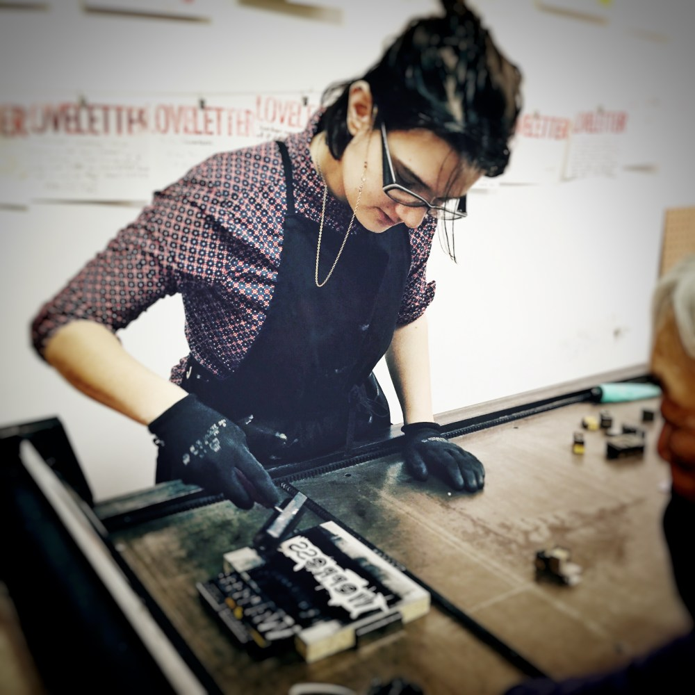 Photo of Cara working on the letterpress. Photo by John Endo Greenaway.