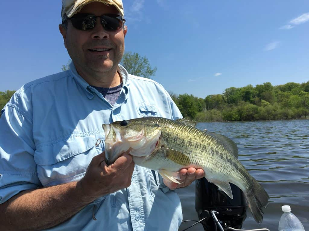 Man holding a largemouth bass caught in a Spring Lake bayou