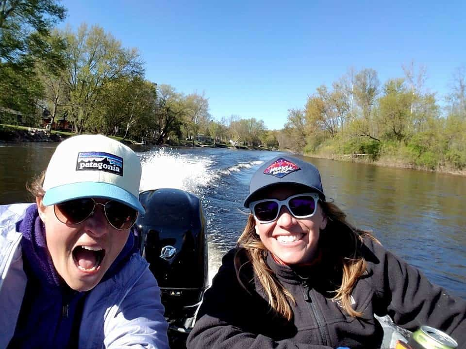 Two women having fun in a moving jet boat on the river