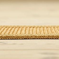brunt sisal boucle tæppe fra siden med overlock kant