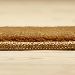 bruntfarvet løst tæppe med kantbånd fra WeRug