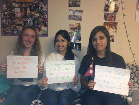 Wesleyan students Teresa Paterson '16, Alisse Singer '16, and Sadichchha Adhikari '16 pose with signs supporting Tunisia.