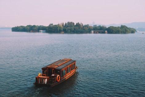łódź w drodze na jedną z czterech sztucznych wysp na jeziorze - wyspa trzech sadzawek odbijających światło księżyca