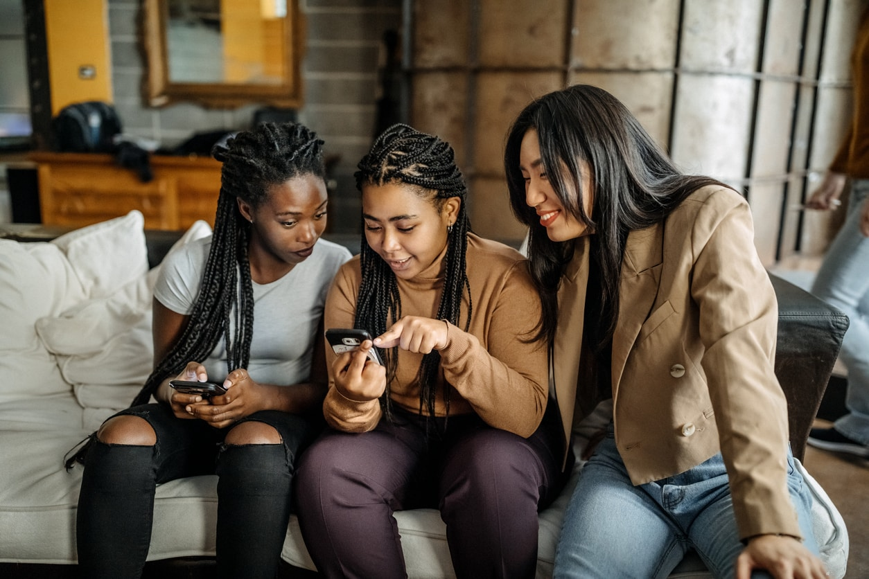 Group of diverse young women using their mobile phones to shop online, a concept of effective Gen Z marketing strategies.