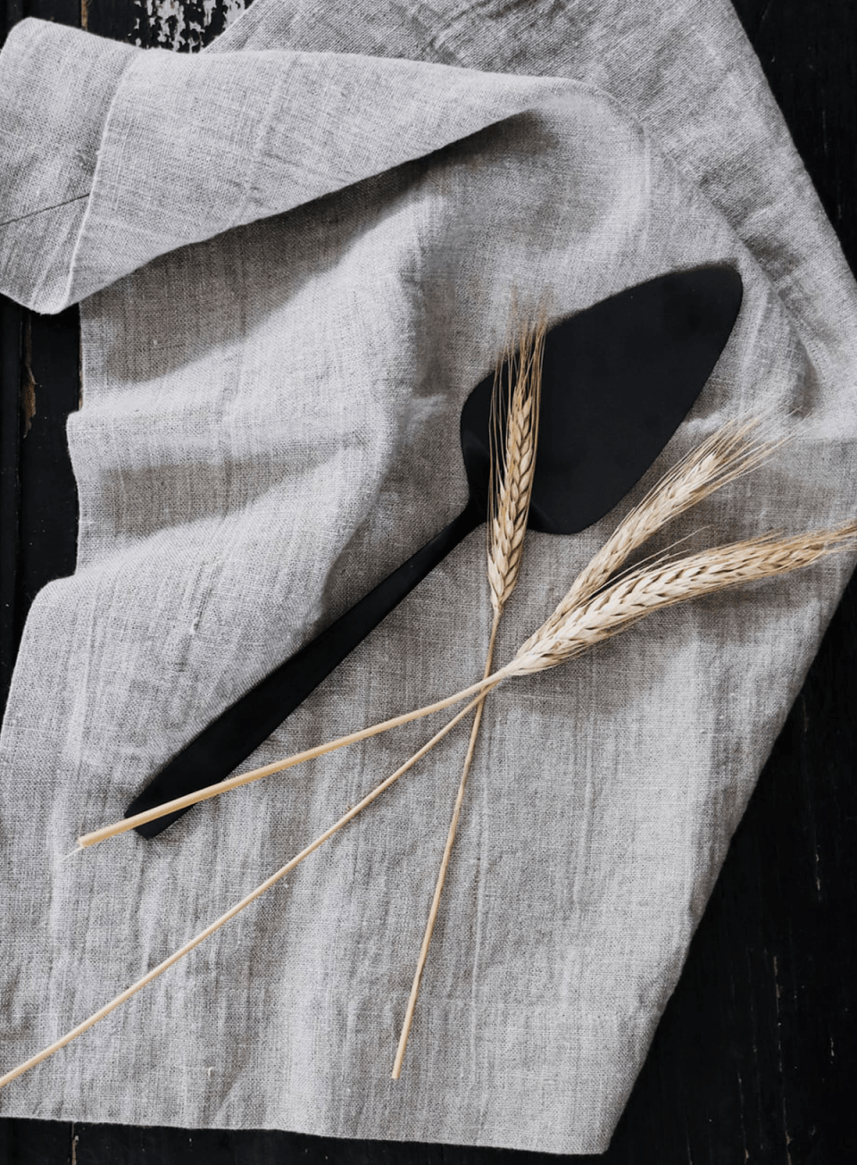 three stalks of wheat laying on a rustic linen napkin next to a pie server with a black finish
