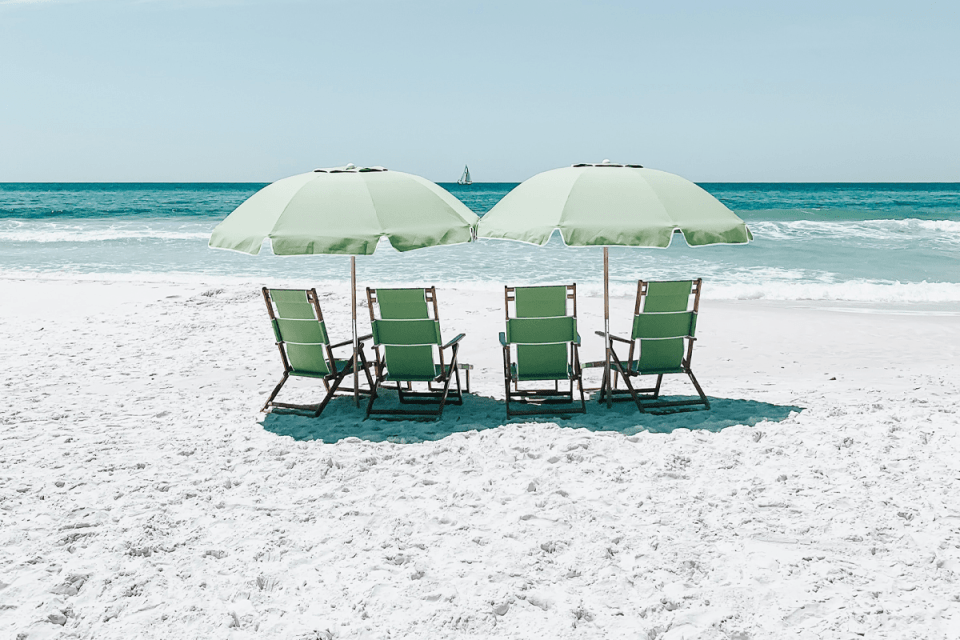 image of four seafoam green folding beach chairs under two matching umbrellas on the sandy beach facing the crystal blue ocean waters in front