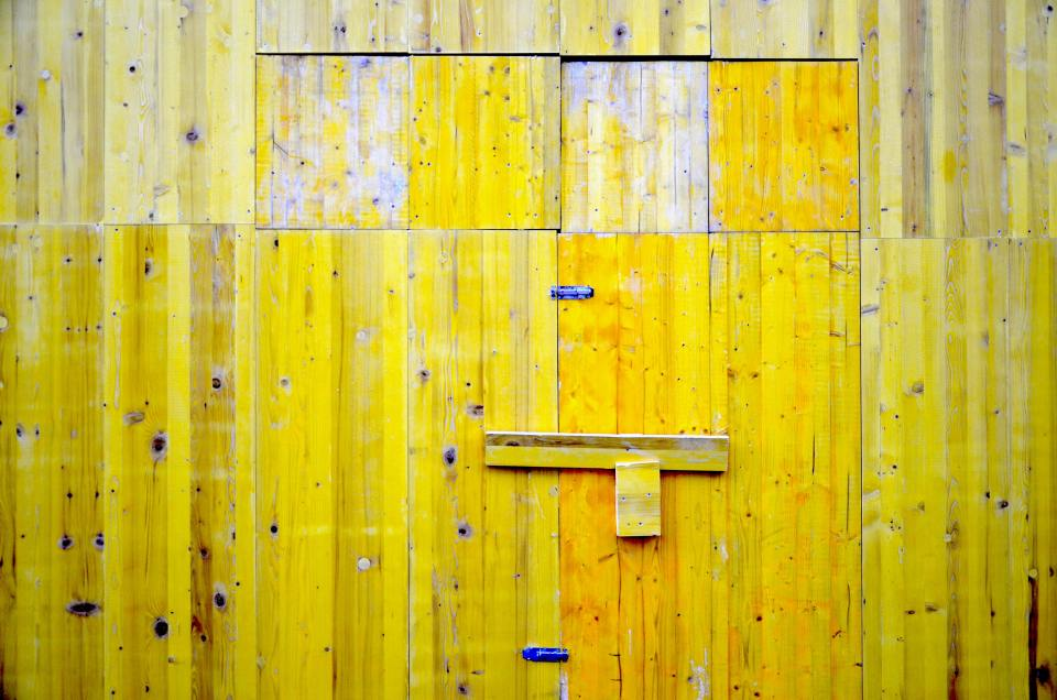 image of barn siding painted vibrant yellow but with weathered sections