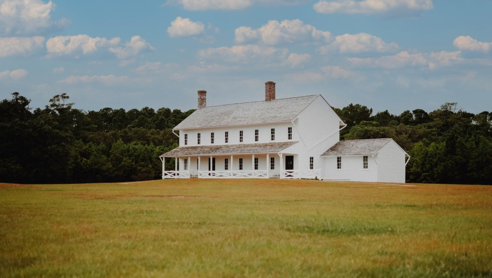 photo of a white two-story farmhouse with wood shake roof and two red chimneys, surrounded by prairie grass and blue sky