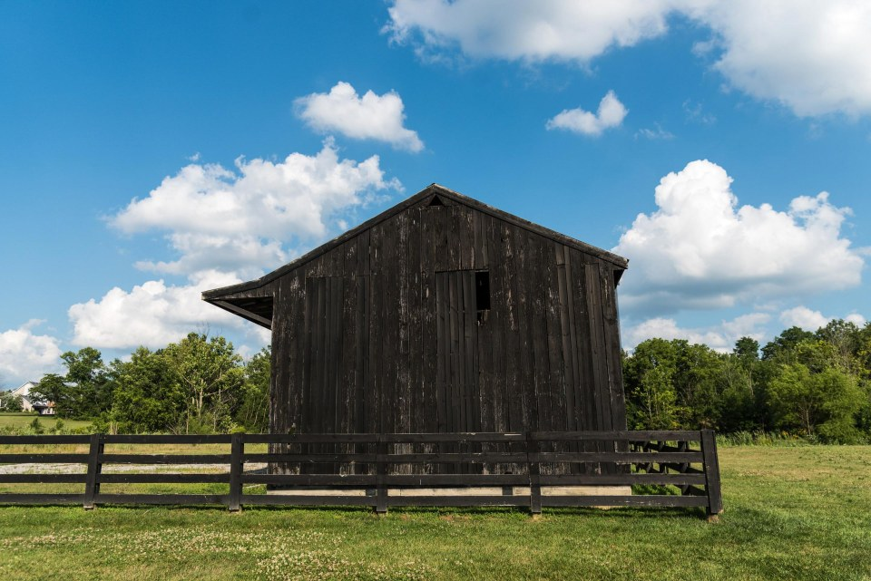 photo of a dark farm building with dark siding and a dark wood fence surrounded by green grass and blue sky