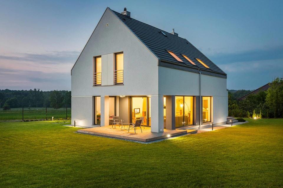 photo of a modern farmhouse at dusk surrounded by green grass and sunset skies