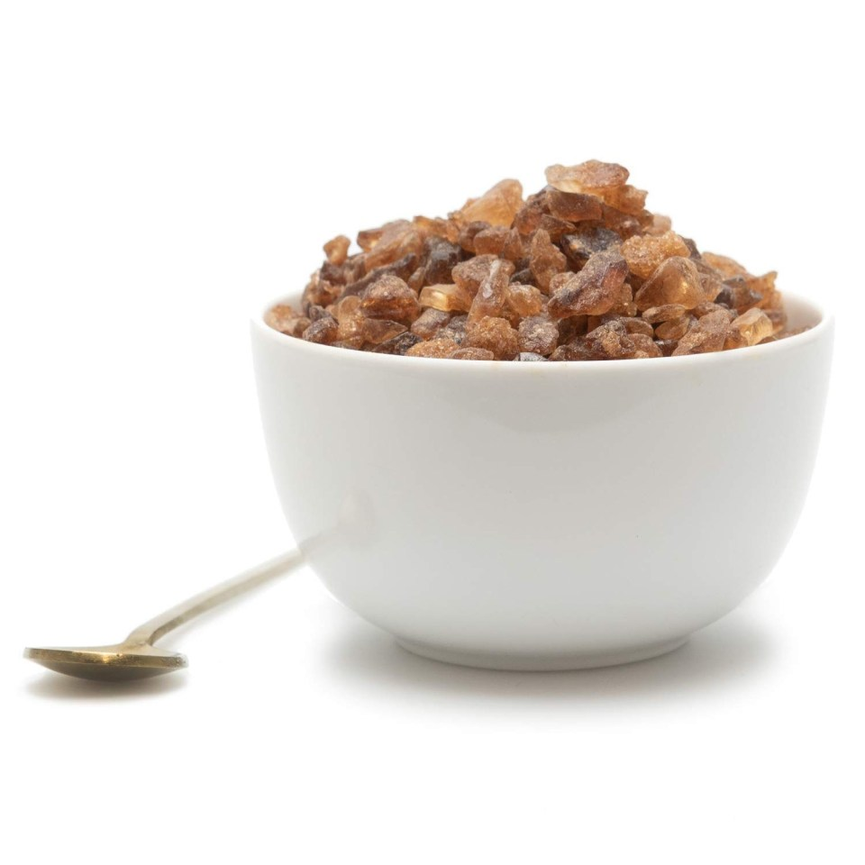amber rock sugar in a white cup with a gold spoon