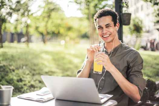 happy man sitting with laptop and juice in park