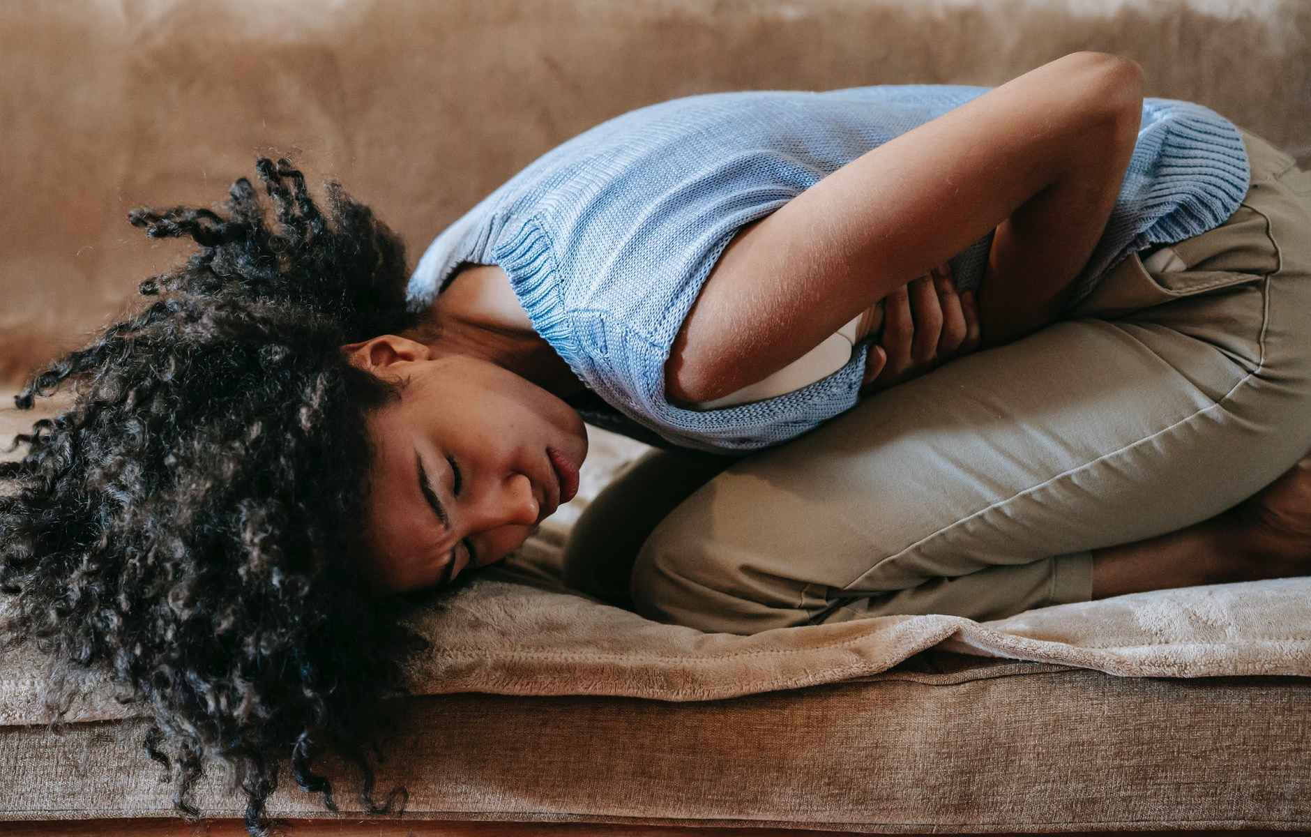 black woman in pain on sofa