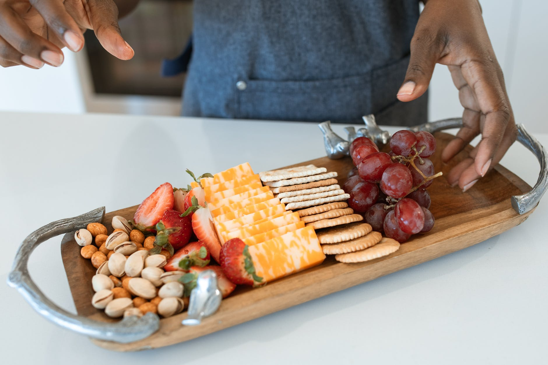 person holding brown wooden tray with sliced fruits