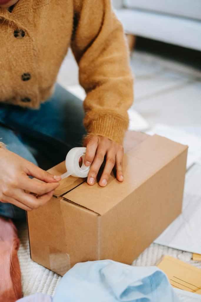 woman preparing carton box with adhesive tape
