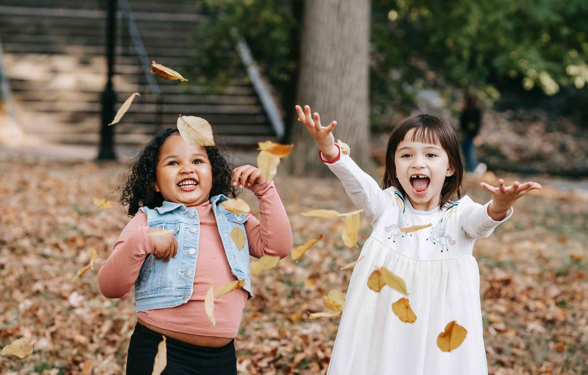 happy kids throwing foliage in park
