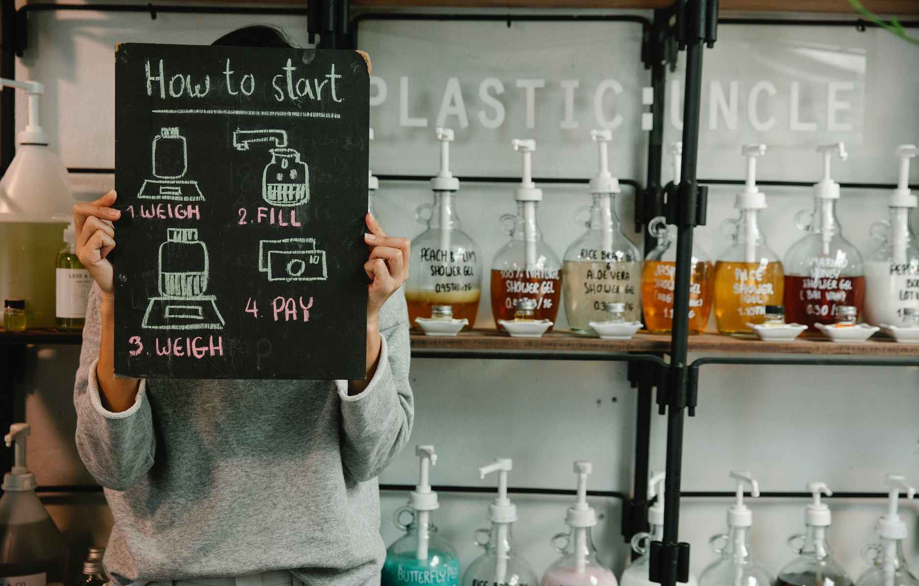 woman showing board with inscription against bottles with pumps in eco shop