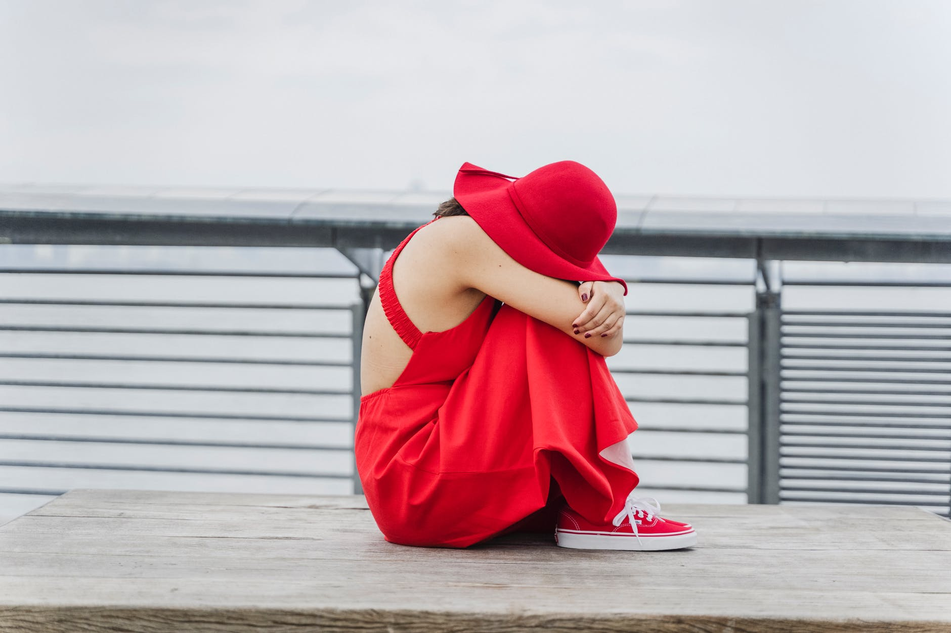 woman in red dress sitting on a wooden bench