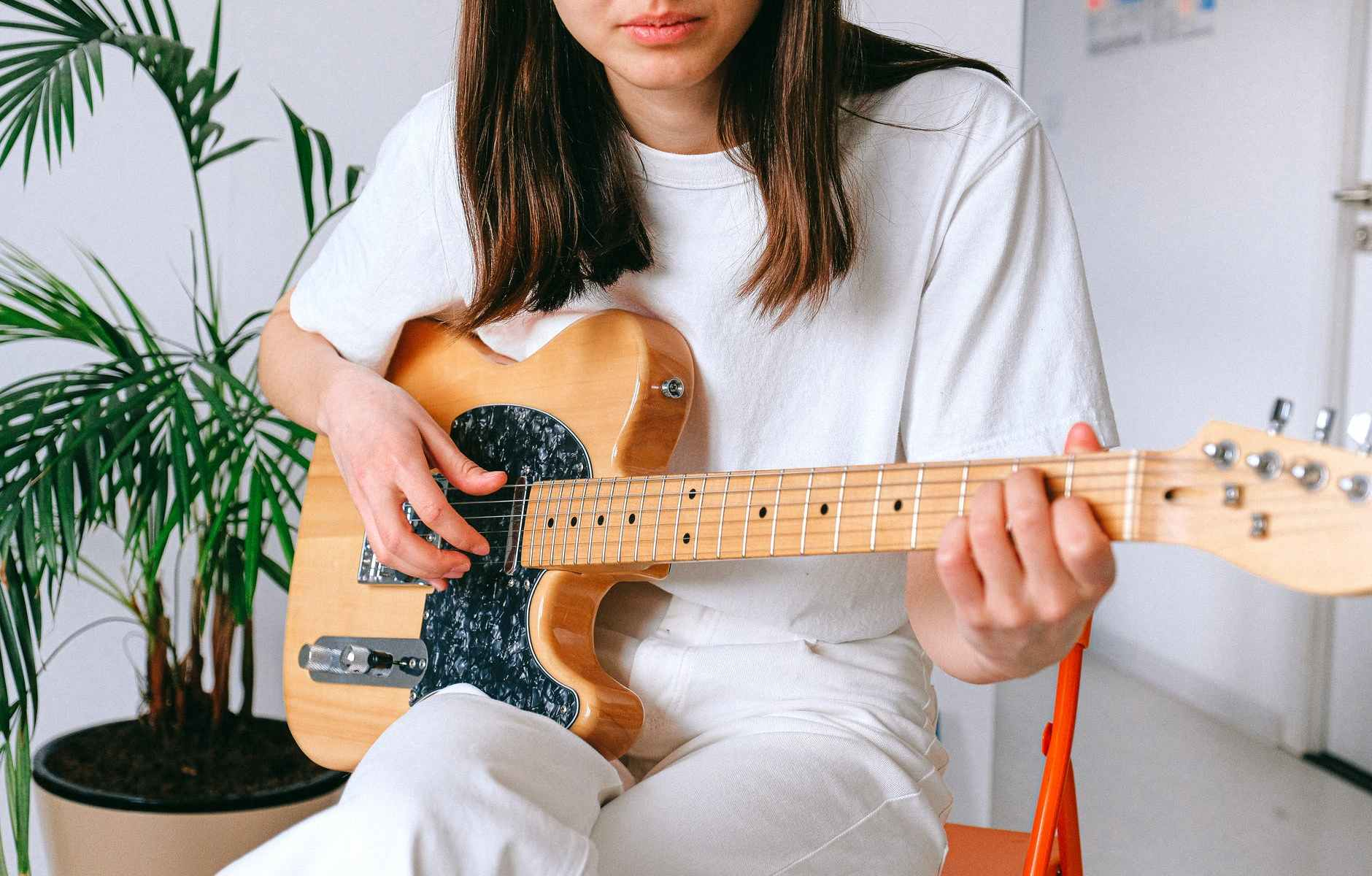 woman in white shirt playing brown electric guitar