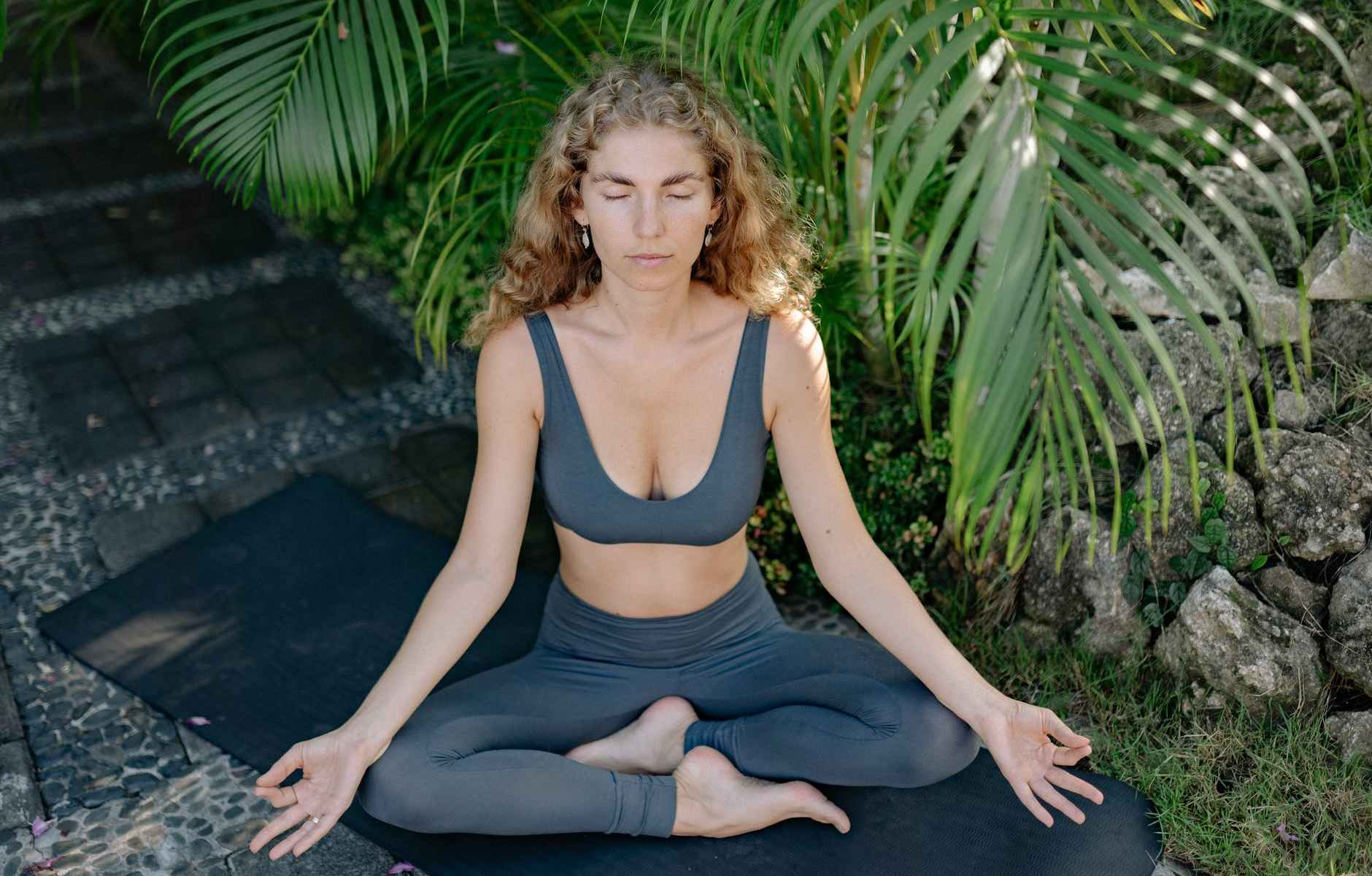 woman in black tank top and gray pants sitting on gray rock