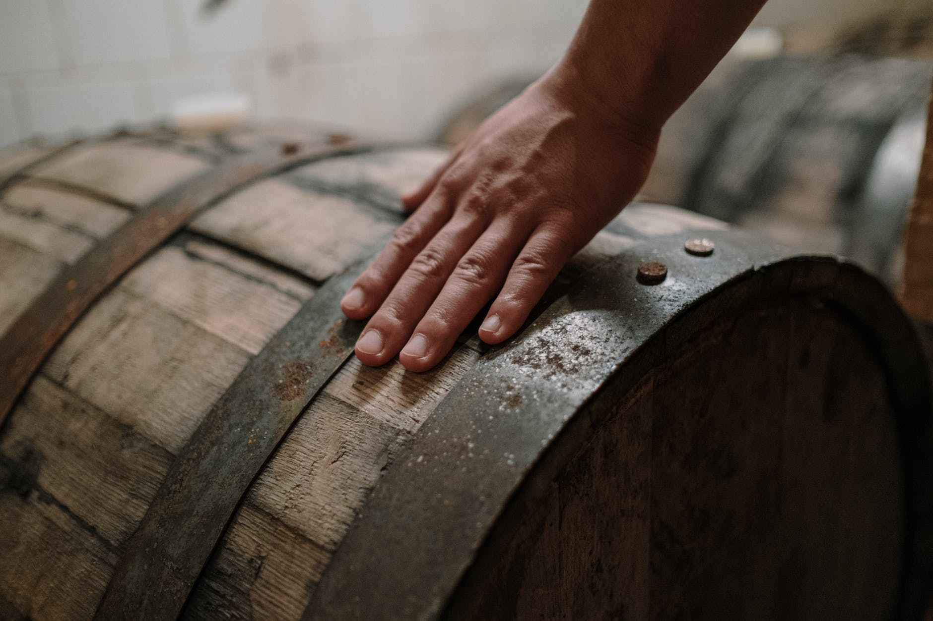 person holding brown wooden barrel