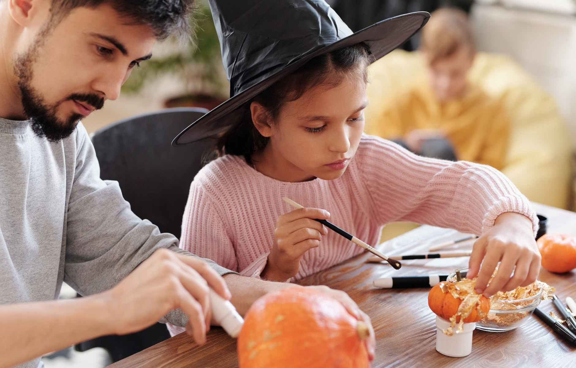 father and daughter decorating pumpkins for halloween