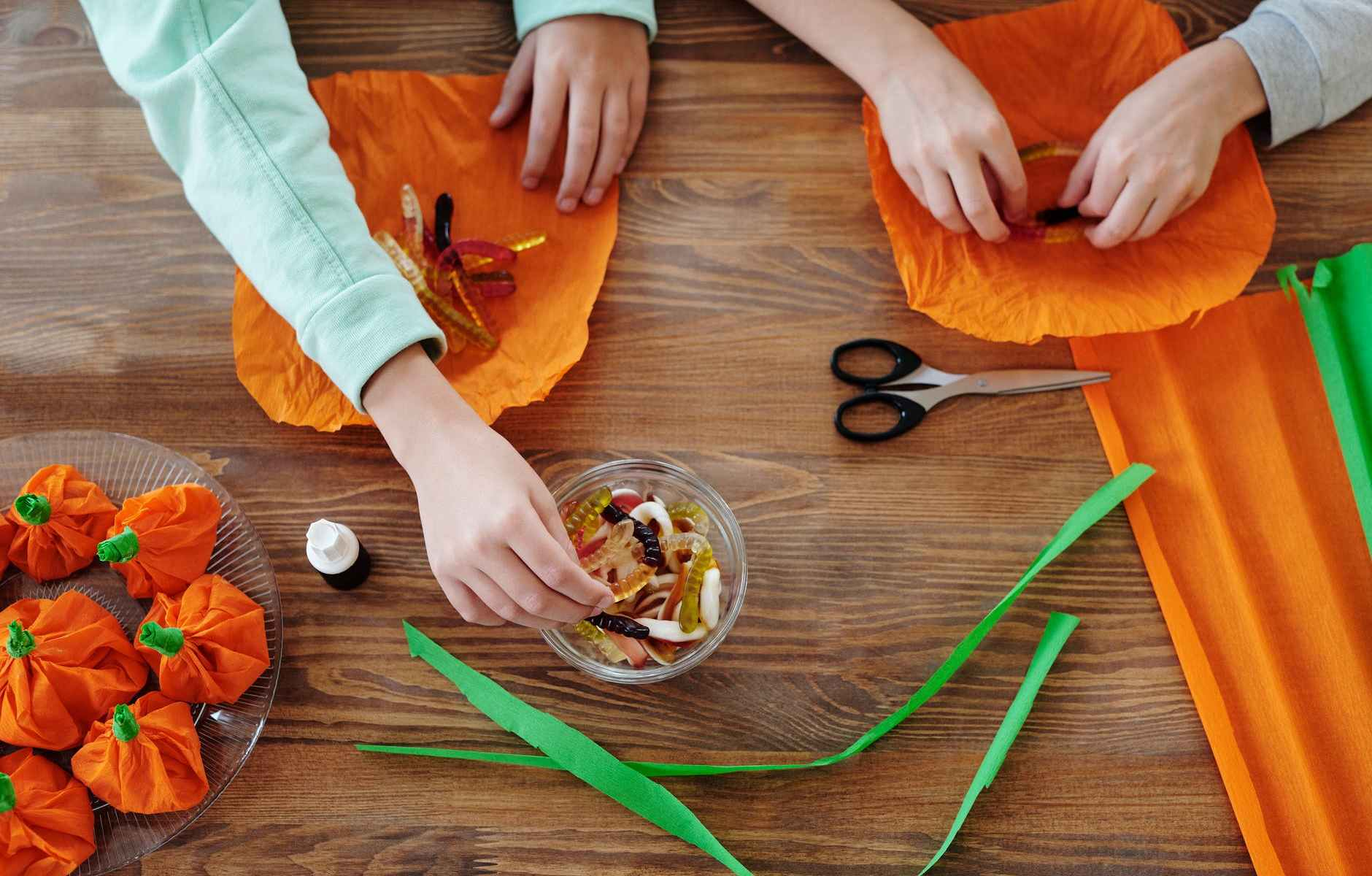 kids wrapping candies in an orange paper