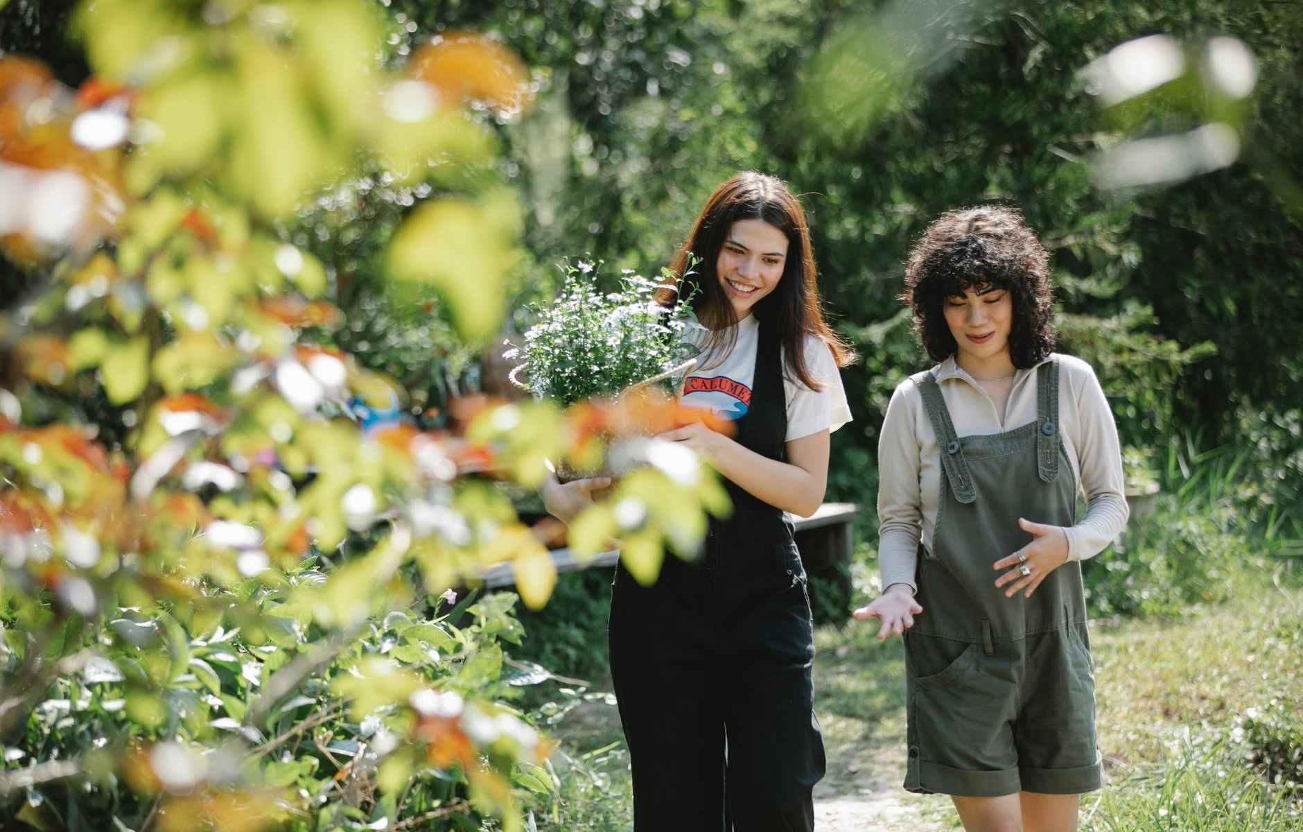happy young friends walking in summer garden