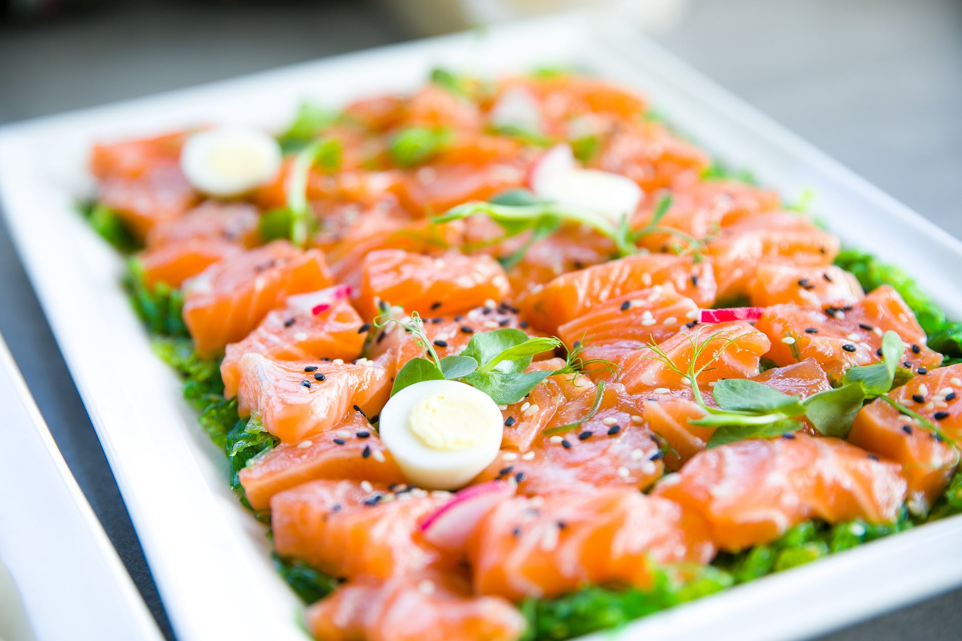 salmon with greens and quail eggs on banquet table