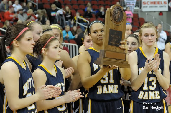 Photo by Dan Hockett Disappointed Senior, Alex Yacko, holds the 'Basketball State Participant' trophy after losing to Top-Ranked Central Lyon in the Class 1A Semifinal Thursday morning at Wells Fargo Arena in Des Moines. Central Lyon defeated Notre Dame, 76-53.