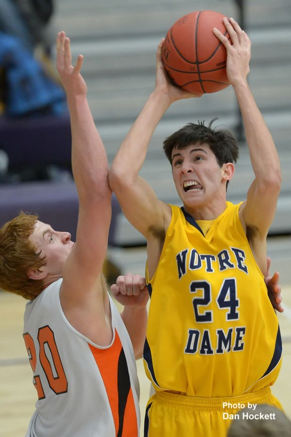 Photo by Dan Hockett Notre Dame's Cole Rinker (24) shoots over Mediapolis' Dalton Scott during Class 2A District 11 final Tuesday night in Burlington. Notre Dame defeated Mediapolis, 53-51.