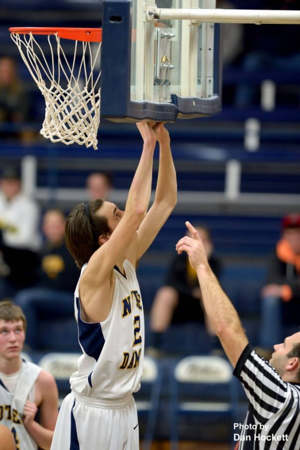 Photo by Dan Hockett Notre Dame's Jeff Giannettino snaps the backboard safety pad back in place after he knocked it loose dunking the ball Thursday night against Central Lee at Father Minett Gymnasium in Burlington. Notre Dame defeated Central Lee, 58-45.
