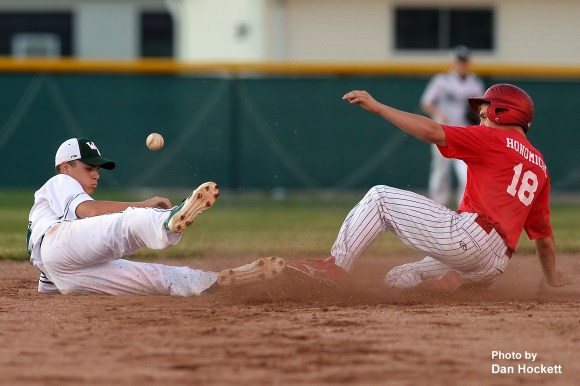 Photo by Dan Hockett Cardinal's Quinn Honomich (right) slides safe to second while West Burlington's Nathan Crooks (left) tries to field the throw Thursday night in West Burlington. Cardinal defeated West Burlington, 5-4.